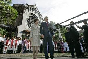 Tổng thống Bush và phu nhân Laura trả lời các phóng viên sau khi cầu nguyện ở nhà thờ Cửa Bắc. Phía đằng sau ông bà là ca đoàn và giáo dân. Ảnh: AP.