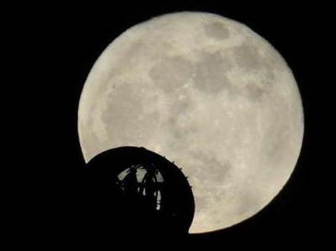 Bóng của những người chơi đu quay London Eye in lên mặt trăng tròn. Ảnh: Reuters.
