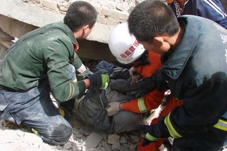 Nhân viên cứu hộ tìm kiếm nạn nhân dưới đống đổ nát sau trận động đất tại tỉnh Thanh Hải, Trung Quốc. Ảnh: AP.