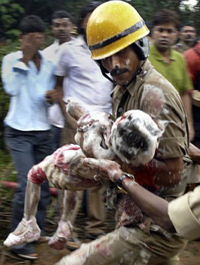 Một em bé còn sống được đưa ra khỏi xác máy bay. Ảnh: AP.