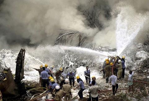 Lính cứu hỏa phun bọt để dập lửa trên xác máy bay. Ảnh: AP.