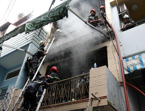 Cảnh sát cứu hỏa làm việc vất vả. Ảnh: An Nhơn.