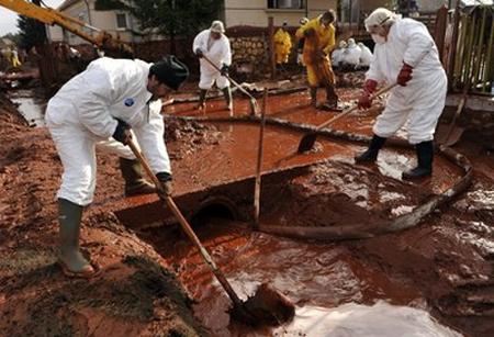 Công nhân dọn bùn trong một làng