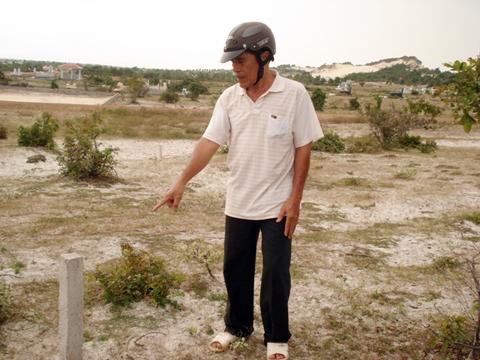 Ông Trương Văn Hải đang chỉ cọc diện tích mua đất nghĩa trang của mình do ông Sơn đóng nhưng không được công nhân vì không có giấy tờ. Ảnh: Hoàng Thái.