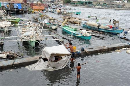 Một em bé đang xem cha buộc lại thuyền. Ảnh: AFP