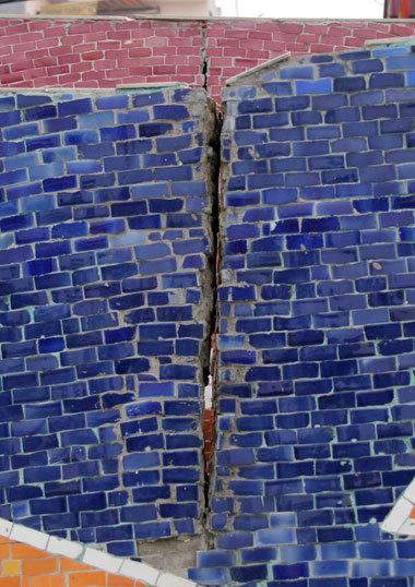 Để hạn chế tình trạng xuống cấp, công ty quản lý bức tường này đã phải xẻ những khe chống rung.
