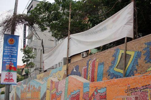Một số hộ dân còn tận dụng bức tường này làm nơi chăng quảng cáo.
