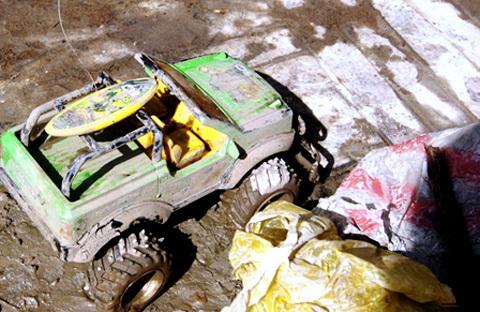 Vừa bước lên tàu hình ảnh đau xót đầu tiên ập vào mắt chúng tôi đó là chiếc xe đồ chơi, quà tặng sinh nhật của cháu Quách Hồng Đạt vẫn còn đó bị nhồi nhét đầy sình bùn