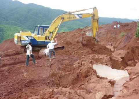 Vụ nổ vỡ ống nước bạt đôi quả đồi, hàng trăm khối nước bùn đá chôn vùi thung lũng bên dưới cùng người phụ nữ mất tích. Đội cứu hộ đang tìm kiếm người mất tích. Ảnh: Lưu Quỳnh