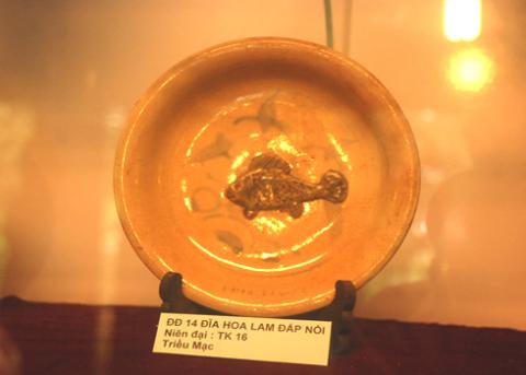 Đĩa gốm hoa lam triều Mạc(thế kỷ 16) đắp nổi hình cá chép trong lòng đĩa được tìm thấy dưới chân tháp Đồng Dương, huyện Thăng Bình(Quảng Nam)- Trung tâm phật giáo của người Chăm lớn nhất Châu Á thời bấy giờ. Ảnh: Trí Tín