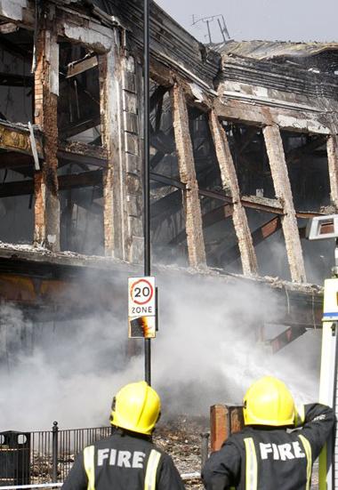 Lính cứu hỏa nhìn một tòa nhà bị thiêu rụi tại quận Tottenham. Ảnh: AP.