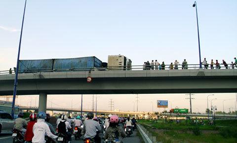 Xe container 40 feet chở nước keo lật nhào trên cầu vượt Cát Lái chiều 11/8. Ảnh: Tá Lâm.