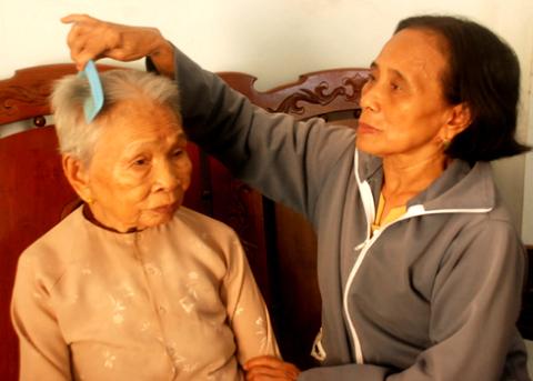 Chị Trần Thị Khen đang chăm sóc mẹ ruột là mẹ Việt Nam anh hùng Võ Thị Khá ở Thị trấn La Hà, huyện Tư Nghĩa, tỉnh Quảng Ngãi. Ảnh: Trí Tín