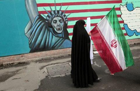 một người phụ nữ Iran đi ngang qua một bức tranh vẽ nhại lại Nữ thần Tự do trên tường sứ quán cũ của Mỹ ở Tehran. Ảnh: AFP.