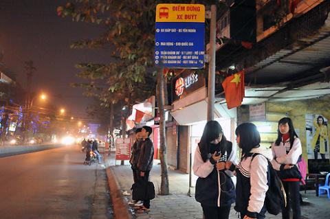 Một số em học sinh trường Kim Liên chờ xe buýt về nhà lúc 19h15 khi phố Phạm Ngọc Thạch khá vắng vẻ.