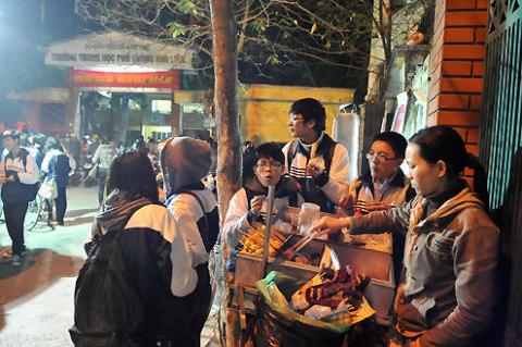 Nhiều học sinh tranh thủ ăn vặt chống đói trước cổng trường.