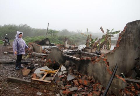 Bà Nguyễn Thị Thương (vợ ông Vươn) bên căn nhà bị đập nát, đốt phá của gia đình tại khu đầm. Ảnh: Nguyễn Hưng.