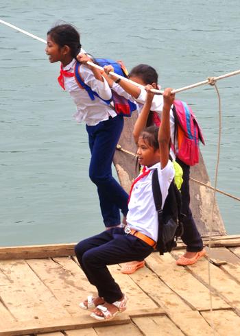 Học sinh đu dây tinh nghịch trên chiếc bè chòng chành trên dòng nước chảy xiết.
