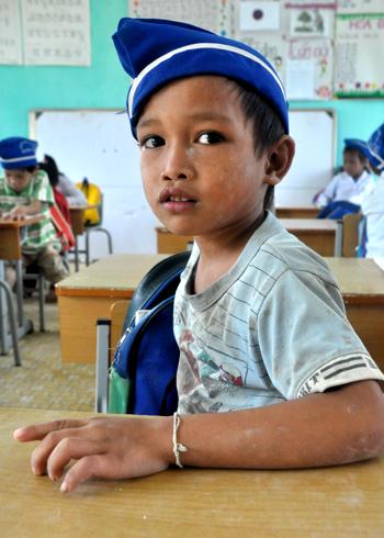 Nhà ở cách xa trường 4 cây số, hàng ngày em Đinh Văn Thương, lớp 1A, trường Tiểu học Sơn Ba phải vượt suối, băng rừng, đu dây đi bè qua sông đến lớp. Ngồi trong lớp học mà cơ thể em lấm lem bùn đất thế này.