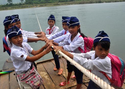 Hàng trăm học sinh ở xã Sơn Ba, huyện miền núi Sơn Hà đu dây thừng kéo bè qua sông mỗi ngày. Ảnh: Trí Tín.