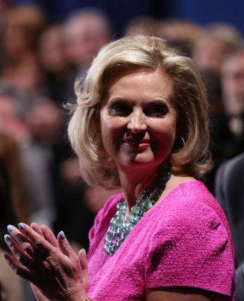 Bà Ann Romney cũng diện váy hồng với tông nhạt hơn chỉ một chút, kèm chuỗi hạt đeo cổ xanh ngọc bích trong.