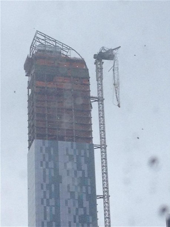 A damaged crane is now dangling from a building on Manhattan's W 57th street. Police have cleared the ground below, while engineers try to figure out the safest way to deal with it.