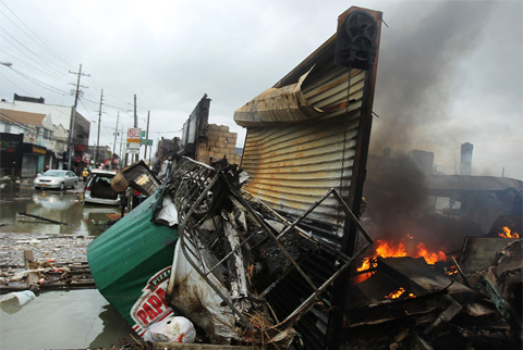 A fire continues to burn Tuesday in the remains of a structure that was destroyed by the Breezy Point blaze.
