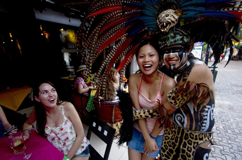Canadian tourists pose for a picture with a Mexican man wearing a pre-hispanic costume at a tourist area of Playa del Carmen in Quintana Roo state, Mexico, on December 18, 2012