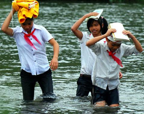Đội áo lạnh, sách vở trên đầu trên đường vượt sông.