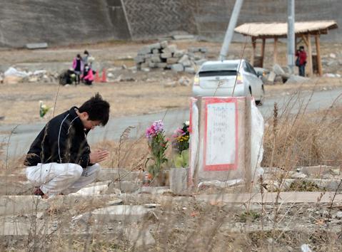 Một người dân cầu nguyện cho những thân nhân thiệt mạng trong
