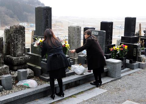 Hai phụ nữ mang hoa tới mộ
