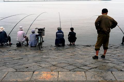 A North Korean man watches fishermen in Wonsan City.