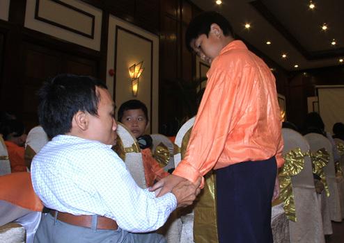 Trẻ khuyết tật giúp nhau chỉnh đốn lại trang phục tại buổi lễ. Ảnh: Nguyễn Đông