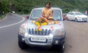 Cô dâu ngồi trên nắp ca-pô ôtô đến đám cưới